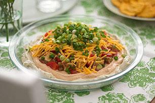 Dip en seis capas de aguacate, queso y verduras