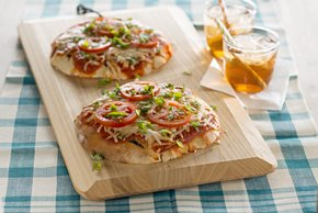 Pizzas a la parrilla de pan pita con tomates y albahaca